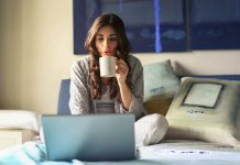 woman-in-grey-jacket-sits-on-bed-uses-grey-laptop